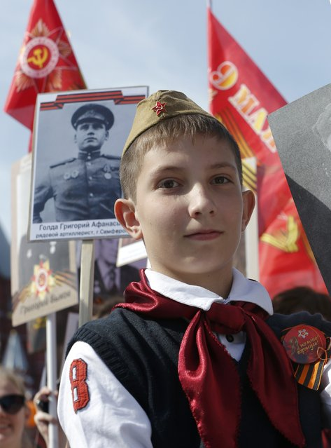 A boy takes part in the Immortal Regiment march during the Victory Day celebrations at Red Square in Moscow, Russia, May 9, 2015. (Photo by Maxim Shemetov/Reuters)