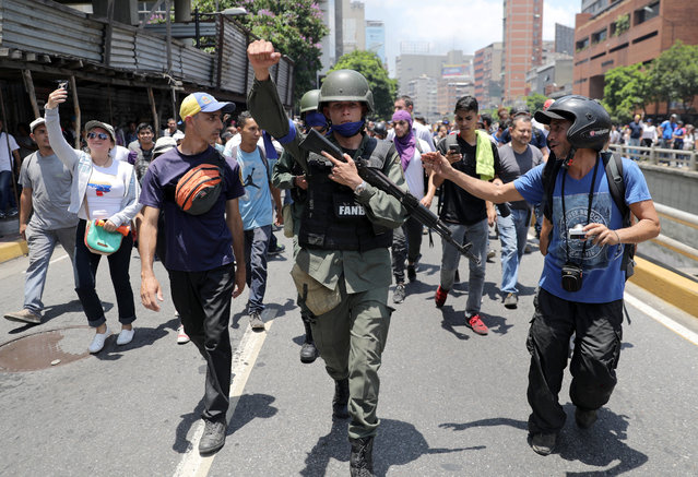 A Venezuelan National Guard member gestures, after joining anti-government protesters in a march, showing his support for opposition leader Juan Guaido in Caracas, Venezuela April 30, 2019. (Photo by Manaure Quintero/Reuters)