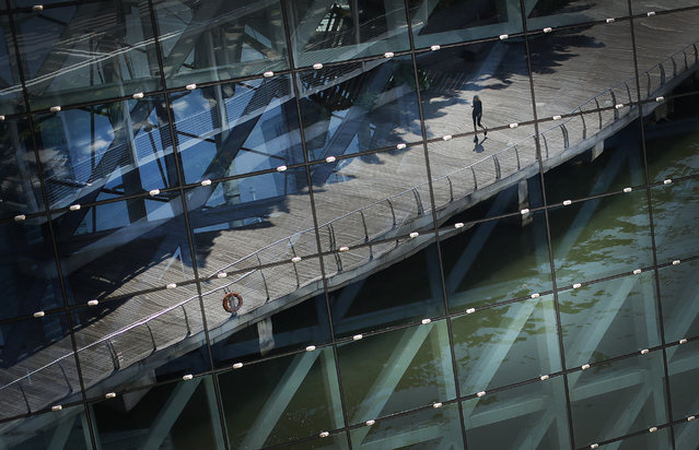 A tourist is seen in a reflection off the facade of a shopping mall at the Marina Bay Sands, which is a popular tourist spot with hotels, shopping, and casinos, Tuesday, April 21, 2015, in Singapore. (Photo by Wong Maye-E/AP Photo)