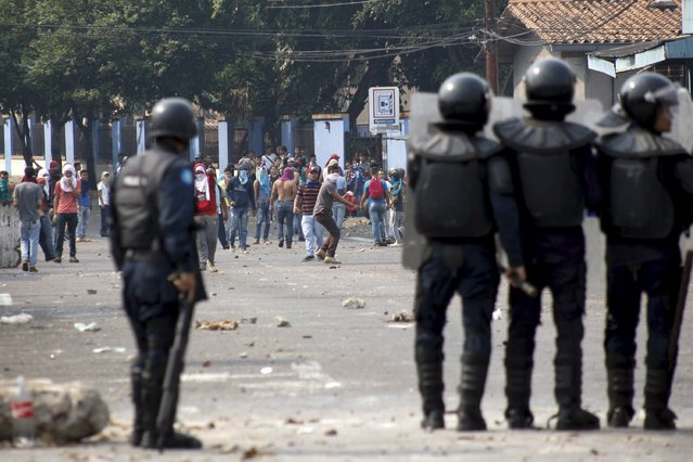 Demonstrators and riot police clash during a protest against the increase in the price of public transport in San Cristobal March 29, 2016. (Photo by Carlos Eduardo Ramirez/Reuters)