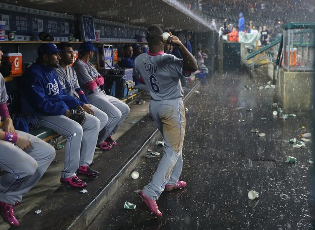 Kansas City Royals' Lorenzo Cain throws a ball to fans during a rain delay in the ninth inning of a baseball game against the Detroit Tigers, Sunday, May 10, 2015, in Detroit. (Photo by Carlos Osorio/AP Photo)