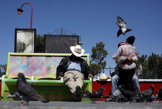 A couple embrace next to a man sleeping on a park bench in downtown Ciudad Juarez, Mexico April 2, 2016. (Photo by Jose Luis Gonzalez/Reuters)
