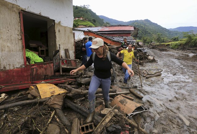 A woman walks in front of the ruins of a house, after a landslide close to the municipality of Salgar in Antioquia department, Colombia May 19, 2015. (Photo by Jose Miguel Gomez/Reuters)