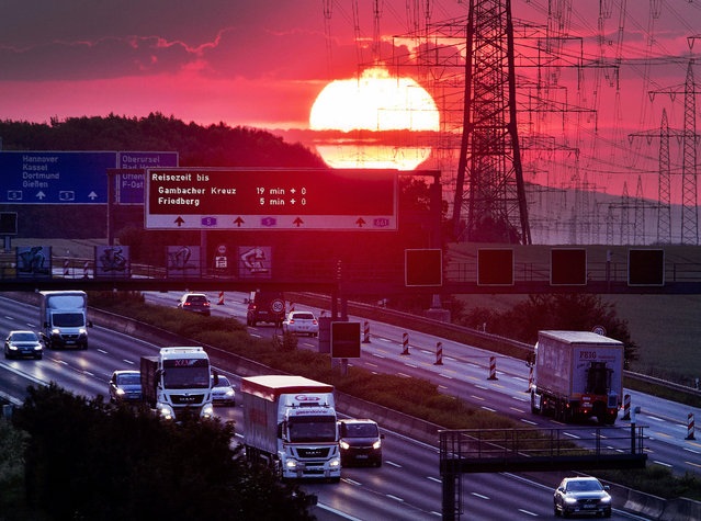 The sun rises as cars and trucks drive on a highway near Frankfurt, Germany, Wednesday, June 5, 2019. (Photo by Michael Probst/AP Photo)