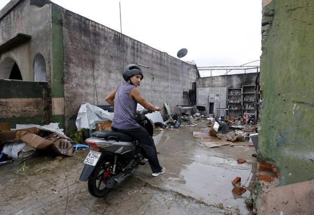 A motorcyclist rides out of a mechanic shop which is seen roofless in Dolores, the day after the city was hit by a tornado, April 16, 2016. (Photo by Andres Stapff/Reuters)