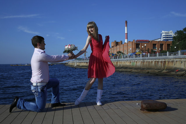 A couple poses foe a picture at a waterfront in the eastern Russian city of Vladivostok, Monday, September 10, 2012. (Photo by Vincent Yu/AP Photo)