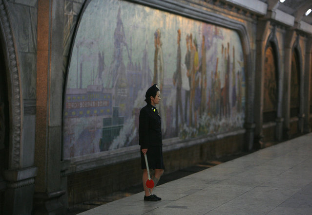 A North Korean station master waits for a train at a metro station in Pyongyang August 27, 2007. (Photo by Reinhard Krause/Reuters)