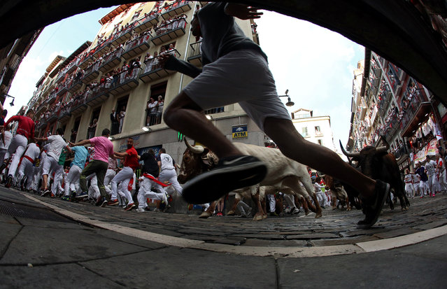 Revellers sprint in front of bulls and steers during the second running of the bulls at the San Fermin festival in Pamplona, Spain, July 8, 2019. (Photo by Jon Nazca/Reuters)