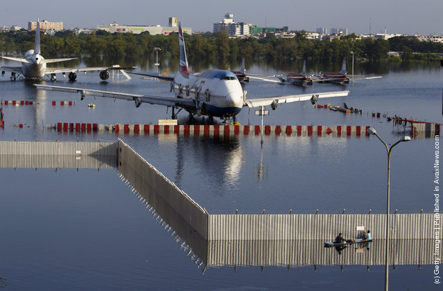 A boat paddles behind a fence near a plane sitting on the flooded tarmack of the closed Don Muang airport