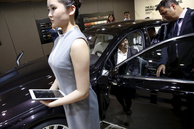 People check out the new BMW M760Li xDrive as it is presented during the Auto China 2016 auto show in Beijing April 25, 2016. (Photo by Damir Sagolj/Reuters)