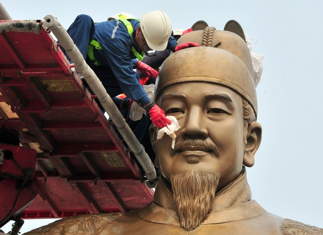 South Korean workers sweep the bronze statue of King Sejong, the 15th-century Korean King, during a street and park spring cleanup event at Gwanghwamun plaza in Seoul on April 10, 2014. (Photo by Jung Yeon-Je/AFP Photo)