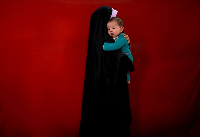 "An Afghan woman holds her child as she visits the inauguration of ""Spring of Holy Quran"" exhibition during the month of Ramadan, in Kabul, Afghanistan June 25, 2015. (Photo by Ahmad Masood/Reuters)"