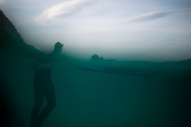 Norwegian surfer Tommy Olsen is seen in the water as he gives a surfing lesson to beginners in Flakstad, near Unstad along the northern Atlantic Ocean on March 9, 2017, where the water temperatures is at five degrees centigrade and the air temperature is at minus two degrees centigrade. (Photo by Olivier Morin/AFP Photo)