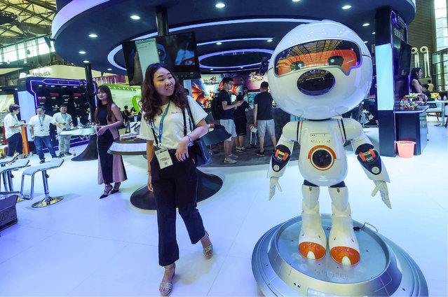 A woman walks past an entertainment robot by Chinese tech firm Sogou during the China Digital Entertainment Expo and Conference, known as ChinaJoy, in Shanghai on August 2, 2019. (Photo by AFP Photo/China Stringer Network)