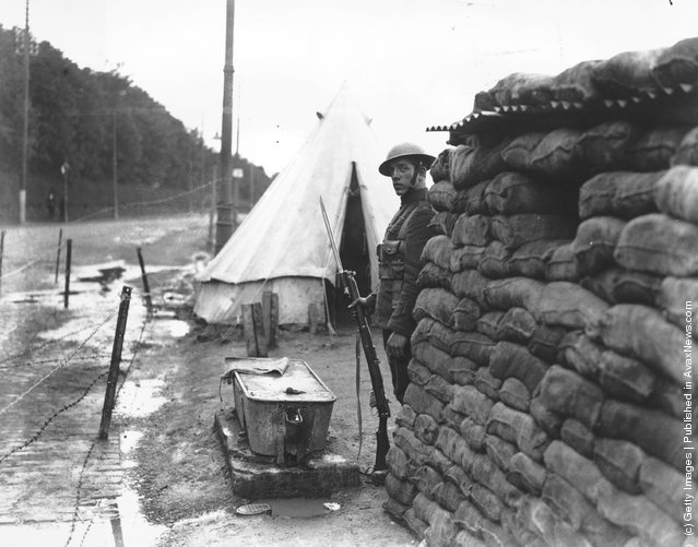 1920: A British soldier on sentry duty outside a sandbagged blockhouse on Orange Day at Belfast
