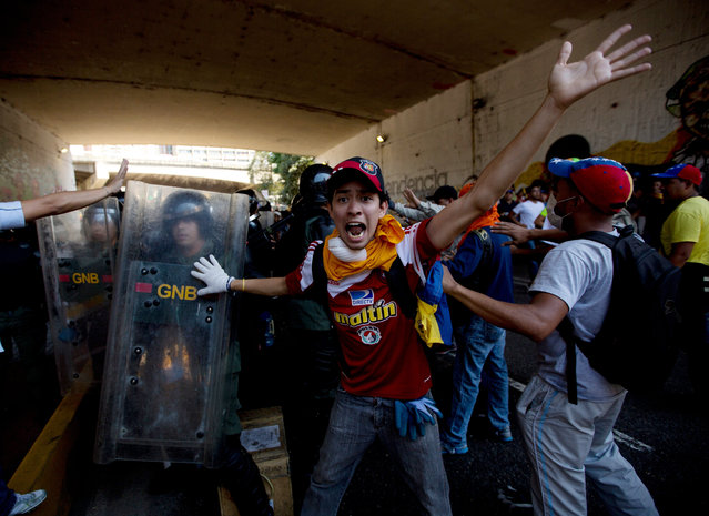 A university student protester shouts for fellow protesters to not attack the Bolivarian National Guards trapped under the highway with protesters on both sides during clashes in Caracas, Venezuela, Saturday, April 12, 2014. Students opposed to the government of President Nicolas Maduro are protesting after leaders of the opposition agreed this week to sit down with Maduro's government for talks aimed at defusing the nation's political crisis, now entering its third month. (Photo by Fernando Llano/AP Photo)