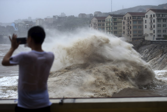 In this August 9, 2019, photo released by Xinhua News Agency, a man uses his mobile phone to record waves crashing on the shore as typhoon Lekima approaches the Shitang Township of Wenling City in eastern China's Zhejiang Province. Typhoon Lekima stuck the coast south of Shanghai, knocking down houses and trees. (Photo by Han Chuanhao/Xinhua News Agency via AP Photo)