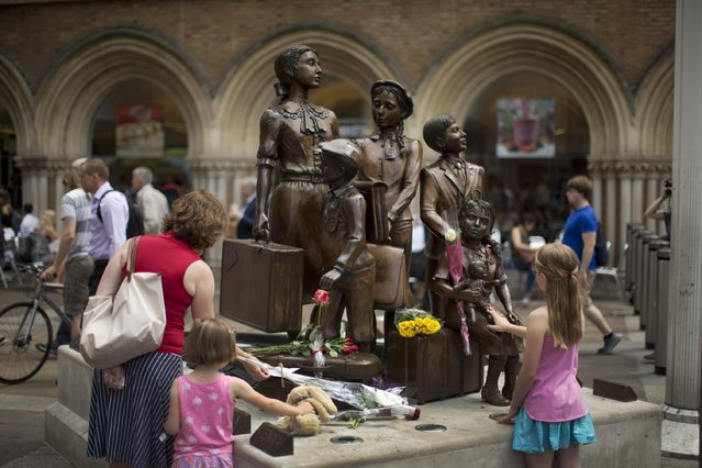 """People look at flowers laid in memory of Britain's Sir Nicholas Winton on German-born Jewish sculptor Frank Meisler's """"Kindertransport"""" (German for children transport) memorial statue outside Liverpool Street Station in London, Thursday, July 2, 2015. (Photo by Matt Dunham/AP Photo)"""