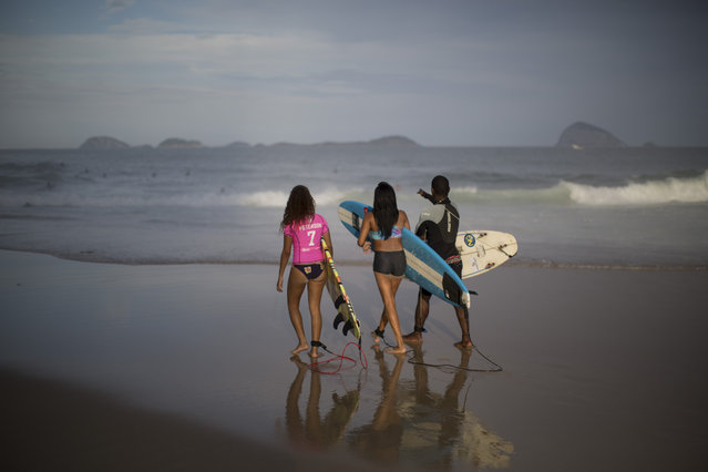 """Rocinha Surf Association, ASR, teacher Carlos Belo, right, instruct young students before entering the water at Sao Conrado brach in Rio de Janeiro, Brazil, Thursday, July 2, 2015. ASR founder Marcio da Silva sees it as a social project, """"We rescue the youth from inside the community, taking them to the beach to teach them the sport while at the same time socializing them"""" he says. (Photo by Felipe Dana/AP Photo)"""