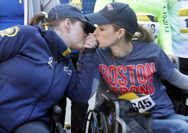 Survivors Erika Brannock, left, and Rebekah Gregory DiMartino, embrace in their wheelchairs as they head to the finish line of the Boston Marathon Tribute Run in Boston, Saturday, April 19, 2014. (Photo by Elise Amendola/AP Photo)
