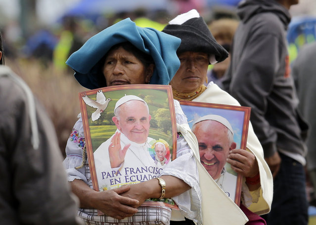 Otavalenas Indians holding posters featuring Pope Francis arrive at Bicentennial Park to attend a Mass celebrated by the pontiff, in Quito, Ecuador, Tuesday, July 7, 2015. The pope's final Mass in Ecuador featured readings in Quichua, the native language most spoken in Ecuador. (Photo by Dolores Ochoa/AP Photo)
