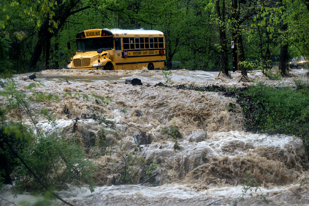 A school bus creates a wake while navigating high water on Bradley Boulevard on April 30 in Bethesda, MD. (Photo by Bonnie Jo Mount/The Washington Post)