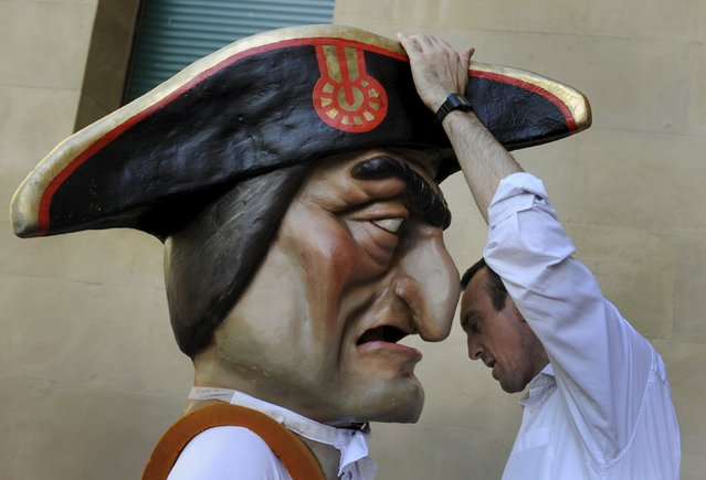 "Kilikis help each other dress during San Fermin festival's ""Comparsa de gigantes y cabezudos"" (Parade of the Giants and Big Heads) in Pamplona, northern Spain, July 8, 2015. (Photo by Eloy Alonso/Reuters)"