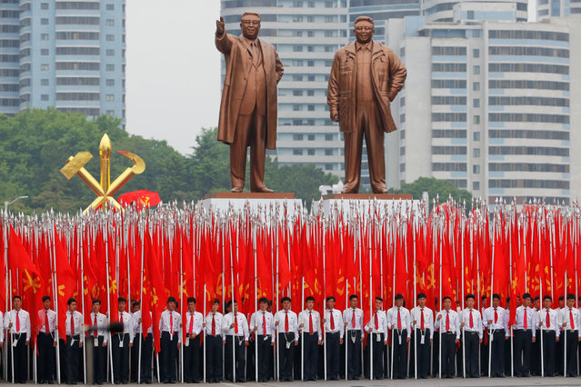 Students carrying party flags stand under statues of former North Korean leaders Kim Il Sung and Kim Jong Il at the beginning of a mass rally and parade in the capital's main ceremonial square, a day after the ruling party wrapped up its first congress in 36 years by elevating him to party chairman, in Pyongyang, North Korea, May 10, 2016. (Photo by Damir Sagolj/Reuters)
