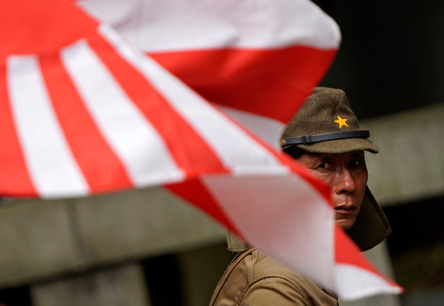 A man dressed as an Imperial army soldier stands behind the Rising Sun war flag at the controversial Yasukuni Shrine in Tokyo, Japan, 15 August 2019, the day of the 74th anniversary of the end of World War II. Some 3.1 million Japanese soldiers and civilians were killed during the war, almost 2.5 million of whom are enshrined at Yasukuni, including convicted WWII war criminals. (Photo by Franck Robichon/EPA/EFE)
