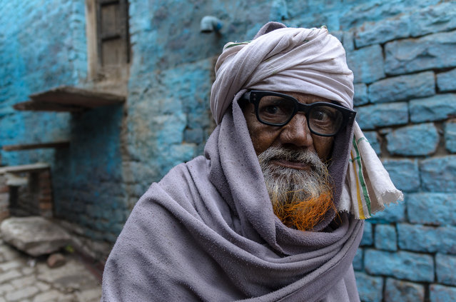 """Red Beard"". Portrait of a 69 years old man, living in the ancient Fatehpur Sikri city, India. I was immediately captured by his aesthetically sense – he liked to color his beard with henna and I really loved his Woody Allen style glasses – and cannot miss the shoot with the nice blue background. Photo location: Fatehpur Sikri, India. (Photo and caption by Emanuele Matarazzo/National Geographic Photo Contest)"