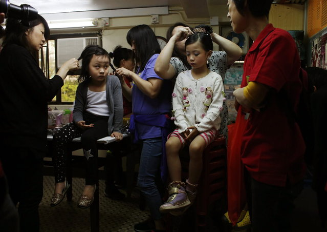 Nicole Kwok (R), 6, receives hair dressing as Tammy Lau, 5, looks on before they took part in a Bun Festival parade at Hong Kong's Cheung Chau island May 6, 2014. The festival celebrates the islanders' deliverance from famine many centuries ago and is meant to placate ghosts and restless spirits. (Photo by Bobby Yip/Reuters)