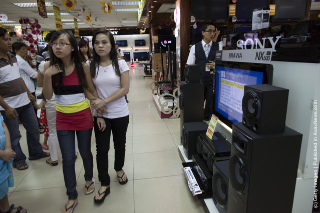 Vietnamese shoppers browse for new TV's at a electronics store