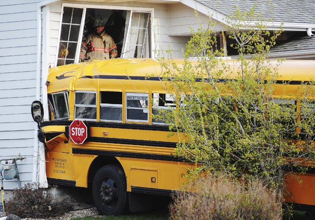 Rescue personnel work a site where a bus crashed into a house, Tuesday, May 6, 2014, in Sioux Falls, S.D. Police say the bus hit one house, then crossed the street and crashed into another house. There were no children on the bus at the time of the crash, and the bus driver, 66, was taken to the hospital with a head injury. (Photo by Joe Ahlquist/AP Photo/Argus Leader)