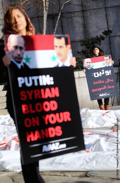 Demonstrators protest against Syrian President Bashar al-Assad and Russian Prime Minister Vladimir Putin next to mock body bags outside United Nations headquarters