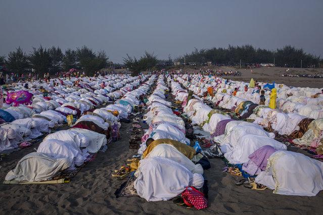 Indonesian muslims perform Eid Al-Fitr prayer on 'sea of sands' at Parangkusumo beach on July 17, 2015 in Yogyakarta, Indonesia. (Photo by Ulet Ifansasti/Getty Images)