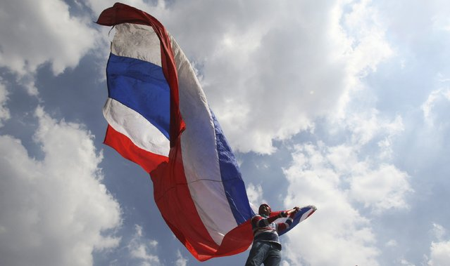 An anti-government protester waves a Thai national flag during a rally Saturday, May 10, 2014, in Bangkok, Thailand. The protesters achieved a partial victory on Wednesday when the Constitutional Court ousted Prime Minister Yingluck Shinawatra, saying she had violated the constitution by transferring a senior civil servant to benefit her politically powerful family. Nine other Cabinet members were also forced from their posts. (Photo by Sakchai Lalit/AP Photo)