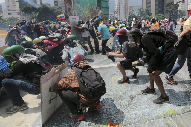 Anti-government protesters face off with Bolivarian National Guard during an opposition march in Caracas, Venezuela, Wednesday, May 10, 2017. (Photo by Fernando Llano/AP Photo)