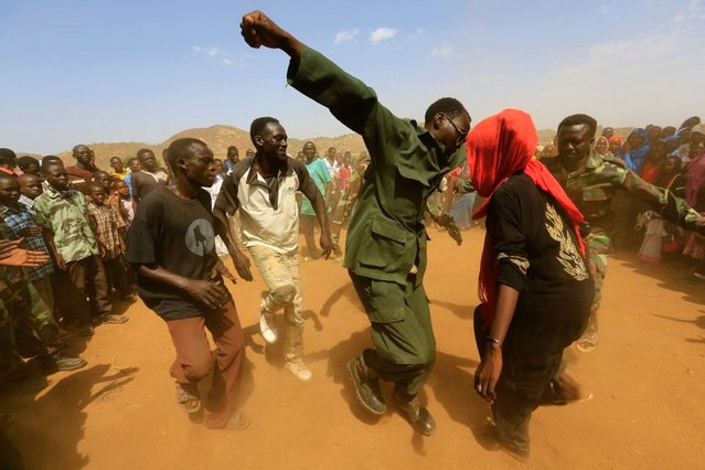Military personnel dance with supporters after claiming to have recaptured the Daldako area, outside the military headquarters in Kadogli, Sudan, from rebels, on May 21, 2014. (Photo by Mohamed Nureldin/Reuters)