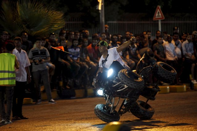"""A youth riding a quad bike performs a stunt during the """"Peace and Security"""" event in Tripoli, Libya July 23, 2015. (Photo by Ismail Zitouny/Reuters)"""
