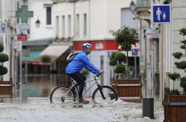 A man cycles in a flooded street near the clinic of Montargis in the Loiret, following heavy rain in France June 1, 2016. (Photo by Christian Hartmann/Reuters)