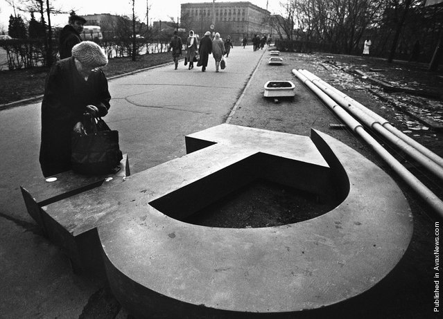 A woman reaches into her bag, which rests on a fallen Soviet hammer-and-sickle on a Moscow street in 1991. December 25, 2011 will mark the 20th anniversary of the fall of the Soviet Union