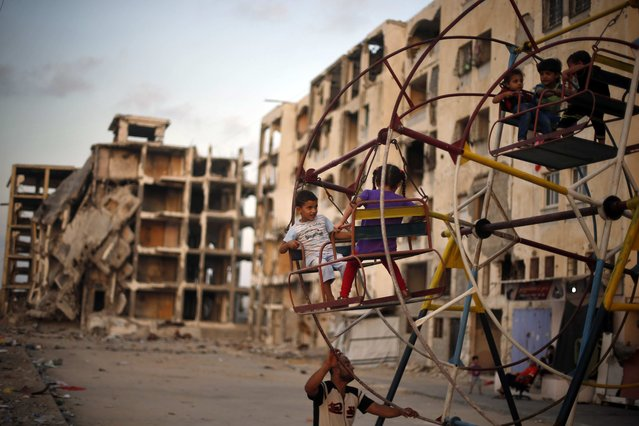 Palestinian children enjoy a ride on a ferris wheel near residential buildings, that witnesses said were destroyed by Israeli shelling during a 50-day war last summer, in Beit Lahiya town in the northern Gaza Strip July 27, 2015. (Photo by Mohammed Salem/Reuters)