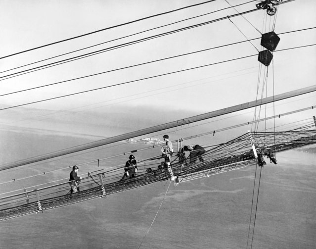 Construction of the Golden Gate Bridge with men on the catwalks working on the cables, San Francisco, California, 1937. Alcatraz Island can be seen in the background. (Photo by Underwood Archives/Getty Images)