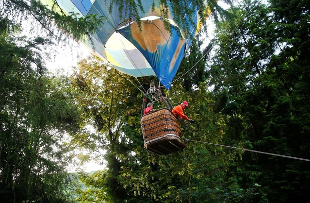 A ballon pilot receives help after landing in a garden by mistake in Bad Honnef near Bonn, western Germany June 10, 2016. (Photo by Wolfgang Rattay/Reuters)
