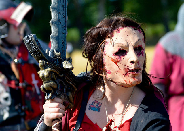 """A participant in the """"ConQuest of Mythodea"""" live action role-playing game stands on a fictional battlefield near Brokeloh, Germany, O6 August 2015. Around 800 participants from around the world are meeting for the 5-day games. (Photo by Eter Steffen/EPA)"""