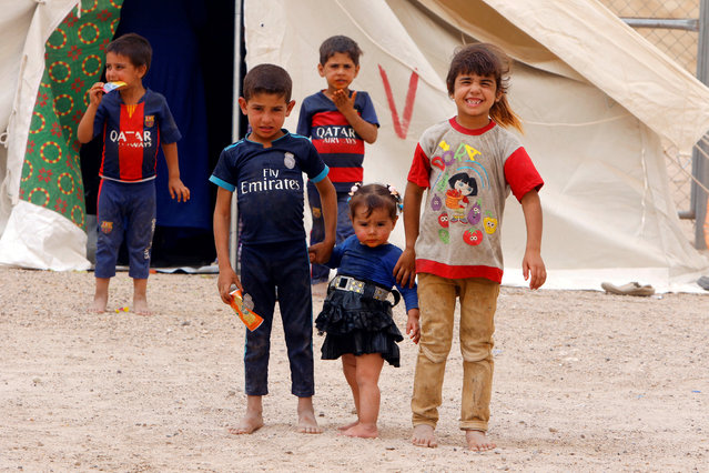 Displaced Iraqi children, who fled from Falluja because of Islamic State violence, pose for photographer during a dust storm at a refugee camp in Ameriyat Falluja, south of Falluja, Iraq, June 16, 2016. (Photo by Ahmed Saad/Reuters)