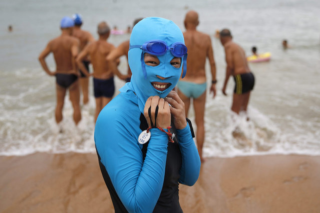 Local swimmer wears a nylon mask at the Huiquan Bay bathing beach in Qingdao city, Shandong province, eastern China, 08 August 2015. The hood is meant to protect the swimmer's face from sun tan, sting injury of jellyfish and insolation. (Photo by Wu Hong/EPA)