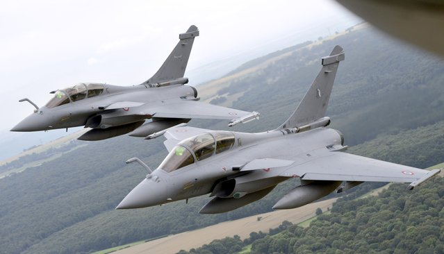 A picture taken on July 14, 2014 from a Boeing C135 refueling tanker shows two French Rafale fighter planes, flying outside the French capital, before taking part in the annual Bastille Day military parade on the Champs-Elysees in Paris. France has issued an unprecedented invitation to all 72 countries involved in World War I to take part in its annual Bastille Day military parade. (Photo by Franck Pennant/AFP Photo)
