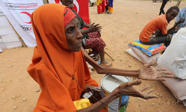 An internally displaced woman who fled flooding of the overflowed Shabelle river talks to the media after receiving relief assistance near Baledweyne town in central Somalia, June 22, 2016. (Photo by Feisal Omar/Reuters)
