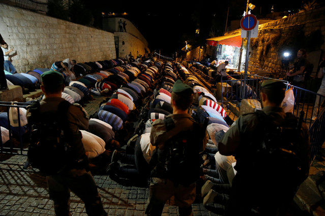 Israeli border police stand guard as Palestinians take part in evening prayers outside the Lion's Gate of Jerusalem's Old City  July 18, 2017. (Photo by Ammar Awad/Reuters)